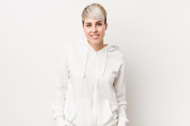 Young curvy woman wearing a white hoodie happy, smiling and cheerful.