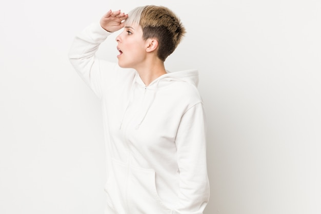 Young curvy woman wearing a white hoodie looking far away keeping hand on forehead.