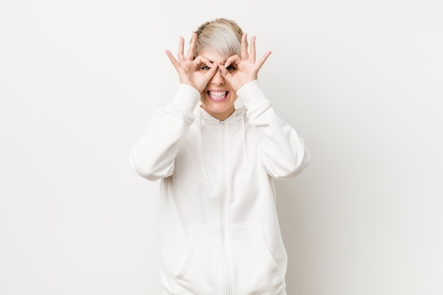 Young curvy woman wearing a white hoodie showing okay sign over eyes