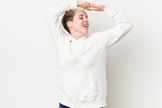 Young curvy woman wearing a white hoodie stretching arms, relaxed position.
