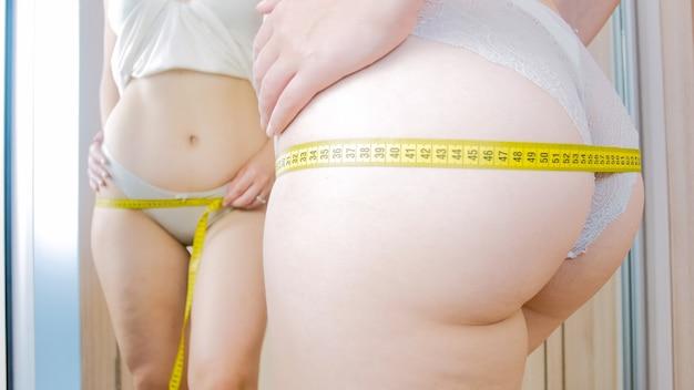 테이프를 측정 하여 그녀의 엉덩이 크기를 측정하는 셀룰 라이트와 젊은 매력적인 여자