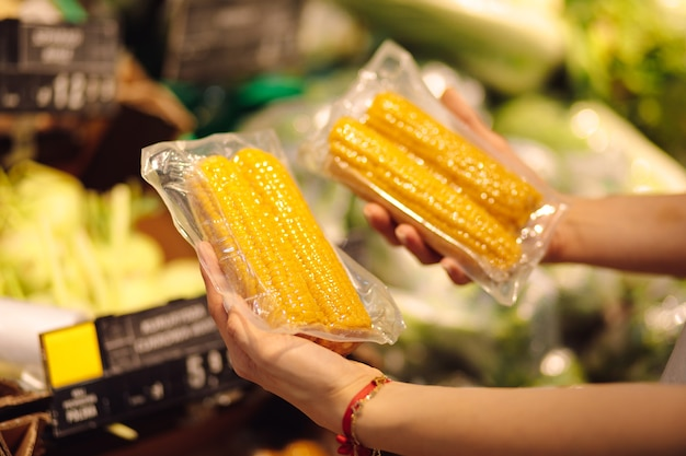 若い顧客は、真空パッケージでスイートコーンの2つのバッグを保持しています。健康食品。正しい生き方。新鮮な野菜とビタミン。家事。