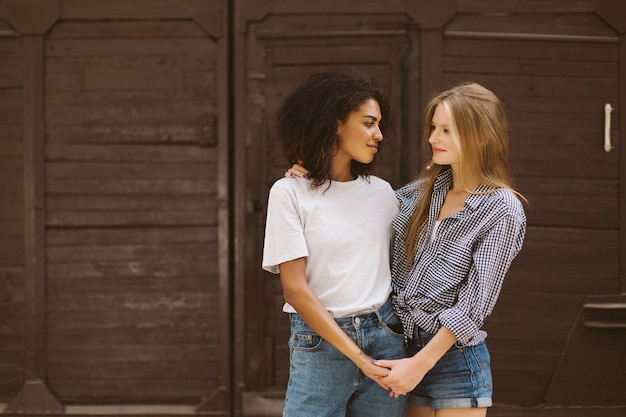 Young cute african american woman with dark curly hair in t-shirt and jeans and woman with blond hair in shirt and denim shorts dreamily looking at each other spending time together outdoor