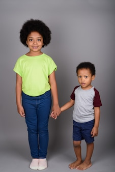 Young cute african brother and sister holding hands