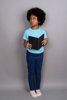 灰色の壁に対して若いかわいいアフリカの女の子