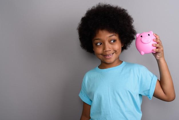 회색 벽에 젊은 귀여운 아프리카 소녀
