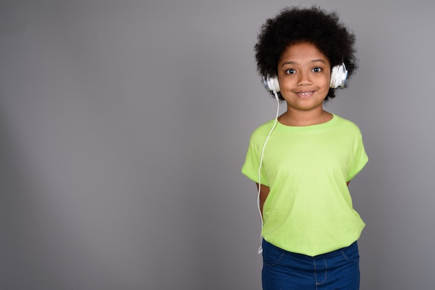 Young cute african girl listening to music against gray wall