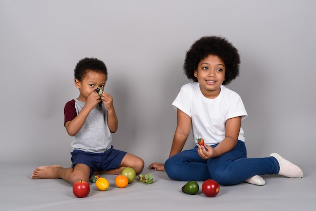 Young cute african siblings together against gray wall