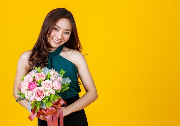 Молодые милые и довольно вьющиеся волосы азиатская женская брюнетка, держащая букет цветов с веселой и счастливой, студийной съемкой, изолированной на ярко-желтом фоне.