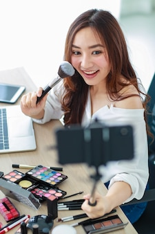 Young and cute asian female vlogger, influencer, or online seller holding smartphone on long stick to take herself video selfie and broadcast live stream for cosmetic review. online marketing concept.