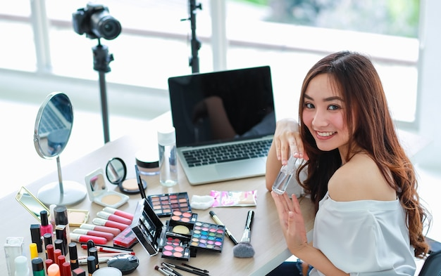 Young and cute asian female vlogger, influencer, or online seller sitting with cosmetics products and dslr camera and laptop notebook computer ready to broadcast online live stream or recording video.