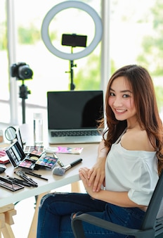 Young and cute asian female vlogger, influencer, or online seller sitting with cosmetics products and dslr camera and smartphone and laptop notebook computer ready to broadcast video live stream.