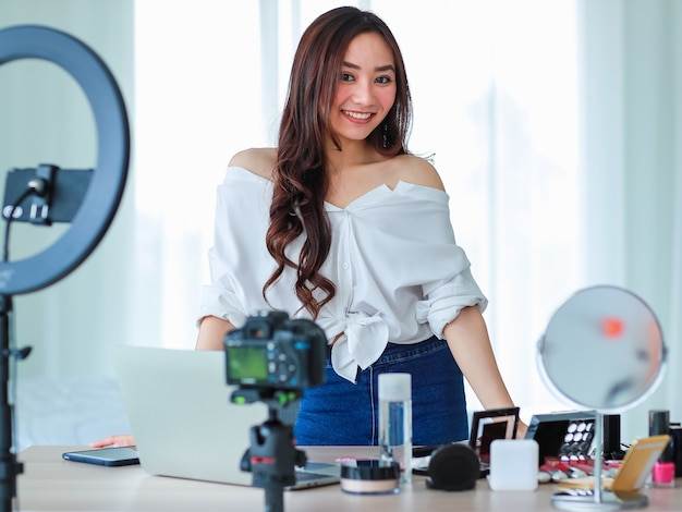 Young and cute asian female vlogger, influencer, or online seller standing with cosmetics products and dslr camera and notebook computer ready to broadcast online live stream or recording video.