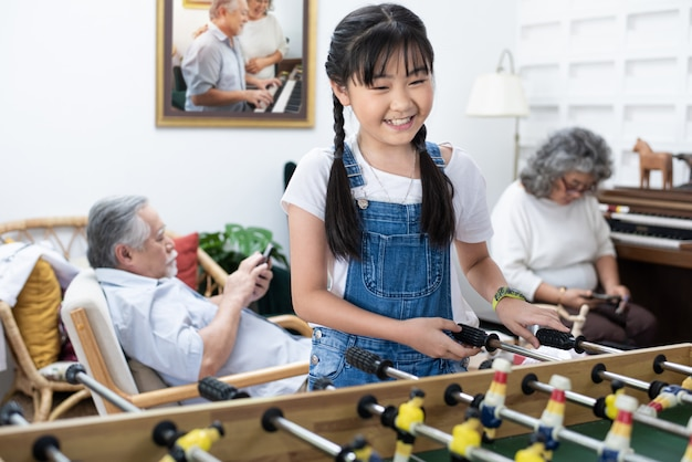 Young cute asian girl playing soccer table game together happily. grandmother and grandfather sit relax beside at home after retirement daily lifestyle. happy healthy family concept.