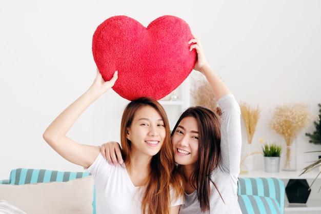 Молодые симпатичные азиатские лесбиянки, держащие красную сердечную форму ивы вместе, улыбаясь с счастью у себя дома