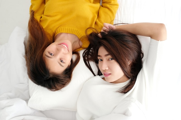 Young cute asian lesbians lying and smiling on white bed together in the morning