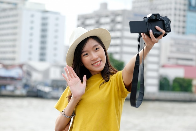 Young cute asian woman in casual style using camera to selfie