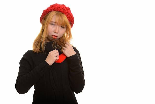 悲しそうに見える胸に赤いハートを持つ若いかわいいアジアの女性