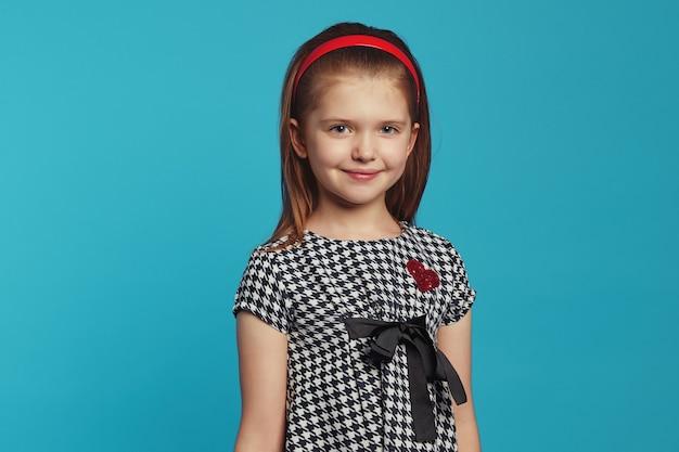 Молодая милая привлекательная девушка в модном платье, улыбаясь на синем фоне
