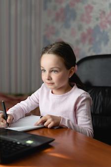Молодая милая девочка учится удаленно.