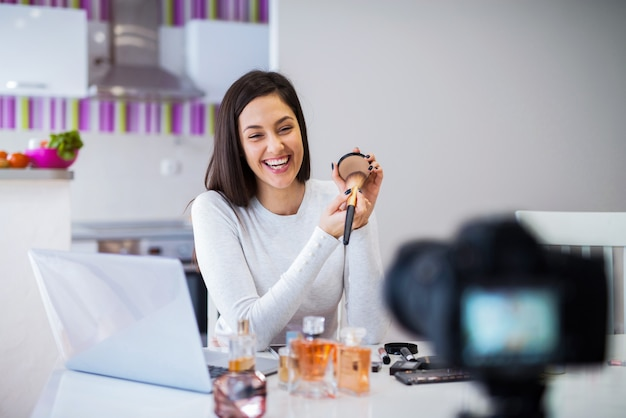 Young cute blogger woman filming her presentation of cosmetic products. sitting in a bright room in front of camera.