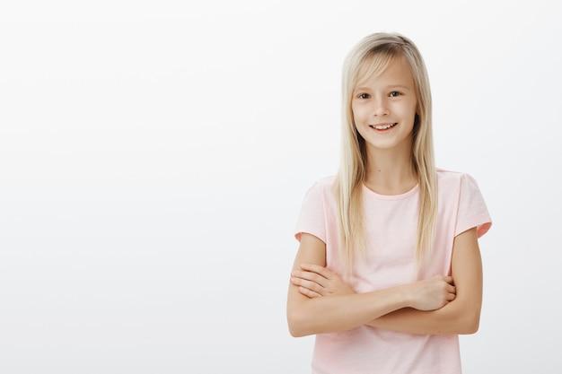 若いかわいい金髪の子供は胸を組んで幸せな笑顔