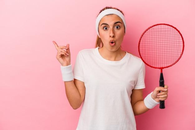 側面を指しているピンクの背景に分離されたバドミントンラケットを保持している若いかわいい金髪白人女性