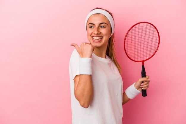 젊은 귀여운 금발의 백인 여자 엄지 손가락으로 멀리, 웃음과 평온한 분홍색 배경 포인트에 고립 된 배드민턴 라켓을 들고.
