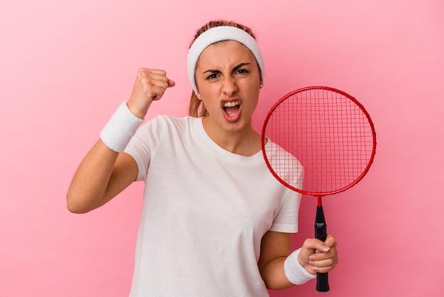ピンクの背景にバドミントンのラケットを持った若いかわいい金髪の白人女性が、カメラに拳を見せ、攻撃的な表情を見せる。