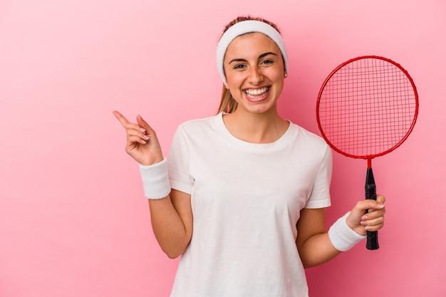 웃 고 옆으로 가리키는, 빈 공간에서 뭔가 보여주는 분홍색 배경에 고립 된 배드민턴 라켓을 들고 젊은 귀여운 금발 백인 여자.