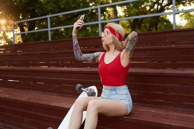 Young cute blonde with tattooed arms in a red t-shirt and denim shorts with a knitted bandana on her head, in red glasses, holding smartphone in hand and makes selfie.