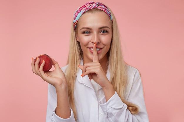 젊은 귀여운 금발의 여자 웃 고 침묵 제스처를 시연, 입 근처에 검지 손가락을 들고, 진정 유지하기 위해 개인 정보 보호를 요구, 서