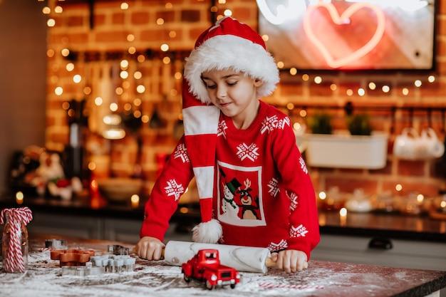 長いサンタの帽子とキッチンでクッキーを作る赤いセーターの若いかわいい男の子