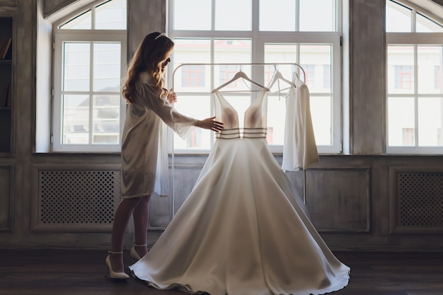 Young cute brunette bride looking at her wedding dress.