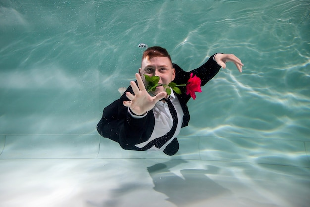 Young cute businessman man in suit gives rose for valentine's day or anniversary on romantic date underwater. gentleman with red rose