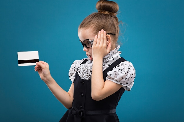 Young cute caucasian girl looking surprised at a credit card