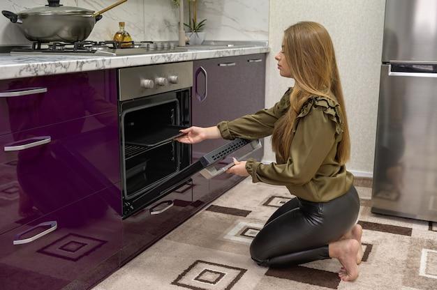 Молодая милая кавказская женщина в черных кожаных колготках, выпечка
