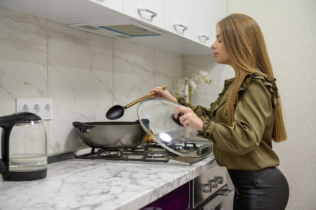 Молодая милая кавказская женщина в черных кожаных колготках готовит