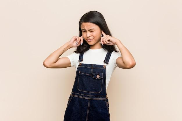 若いかわいい中国のティーンエイジャー手で耳を覆うピンクの壁にコートを着た若いブロンドの女性。