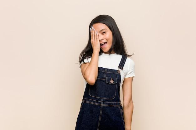 若いかわいい中国の10代の若いブロンドの女性は、手のひらで顔の半分をカバーする楽しいピンクの壁にコートを着ています。