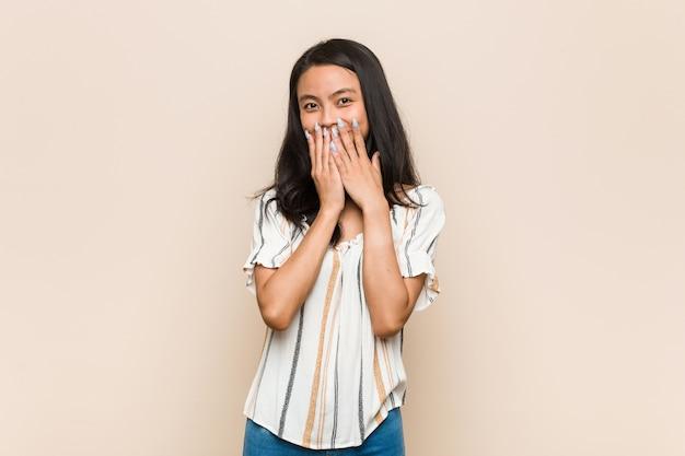 Молодой милый китайский подросток молодая блондинка женщина в пальто у розовой стены смеется о чем-то, прикрывая рот руками.