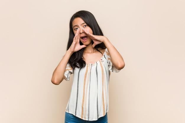 Молодой милый китайский подросток молодая блондинка женщина в пальто против розовой стены кричит возбужденно.