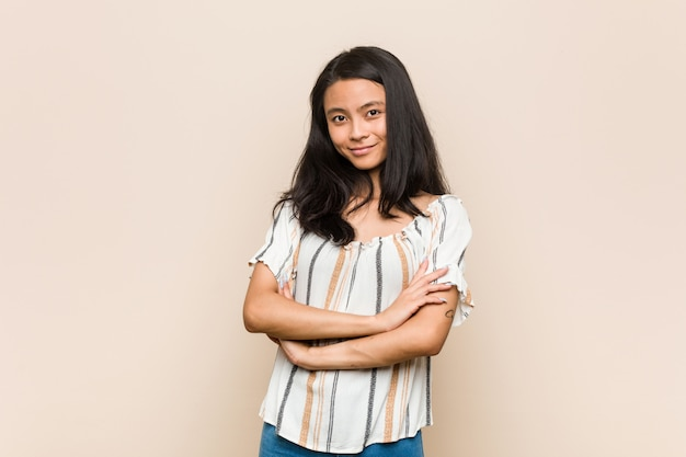 Молодой симпатичный китайский подросток молодая белокурая женщина в пальто на розовой стене, которая чувствует себя уверенно, скрестив руки с решимостью.