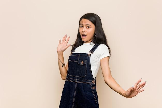 差し迫った危険のためにショックを受けているピンクのコートを着ている若いかわいい中国の10代の若いブロンドの女性