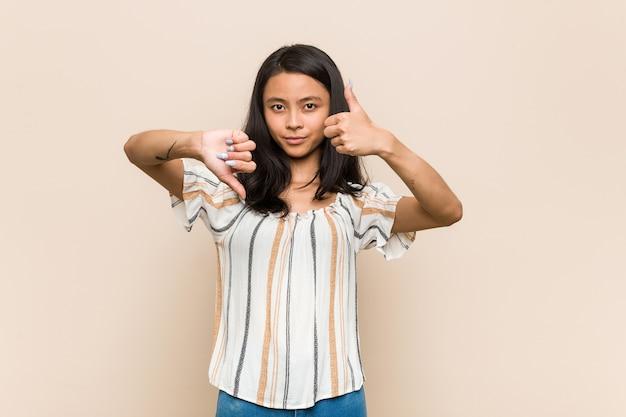 若いかわいい中国のteinager親指を上に、親指を下に表示するピンクに対してコートを着ている若いブロンドの女性、難しい選択の概念