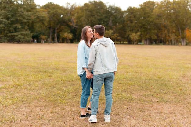 Молодая милая пара держится за руки и смотрит друг на друга на открытом воздухе в парке