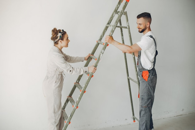 The young and cute couple repairs the room