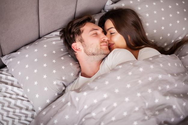 ベッドで一緒に若いかわいいカップル