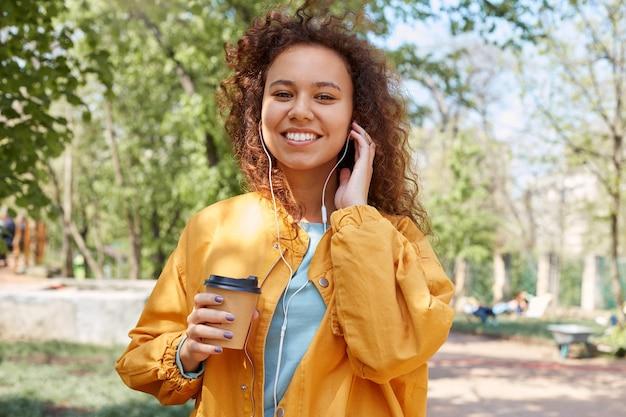 Giovane ragazza carina riccia dalla pelle scura ampiamente sorridente, con in mano una tazza di caffè, indossa una giacca gialla, cammina nel parco, ascolta musica e si gode il tempo.