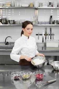Молодая милая женщина-пекарь замешивает тесто в большой миске и улыбается